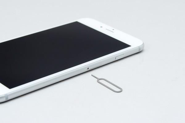 本体右側面にある小さな穴に、SIM取り出しツールの棒を差し込みます