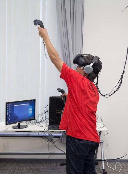 HTC Viveを体験中の筆者。コントローラーはワイヤレスですが、VRゴーグルはケーブルに接続されています